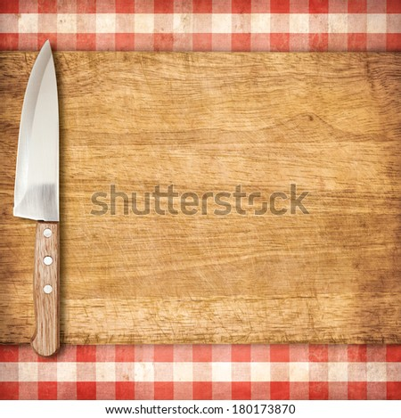 Cutting breadboard and knife over red grunge gingham tablecloth background - stock photo