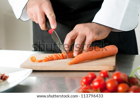 Cutting carrot on a wooden board for meal preparation at restaurant
