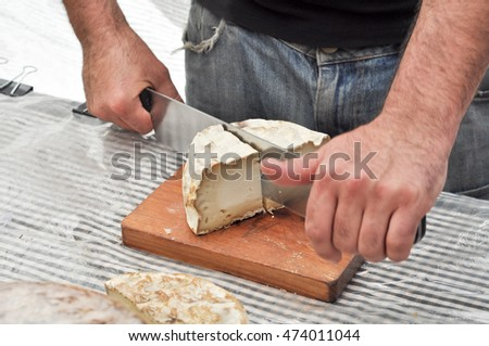 Cutting Catalan goat cheese in the market