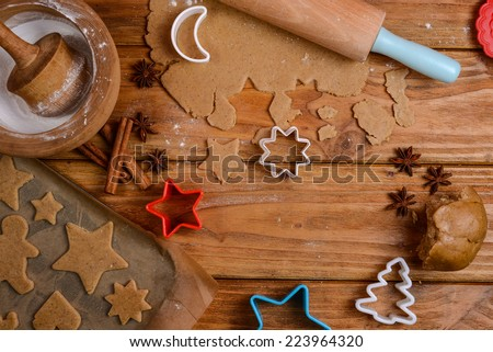 Cutting Christmas cookies on wooden table - stock photo