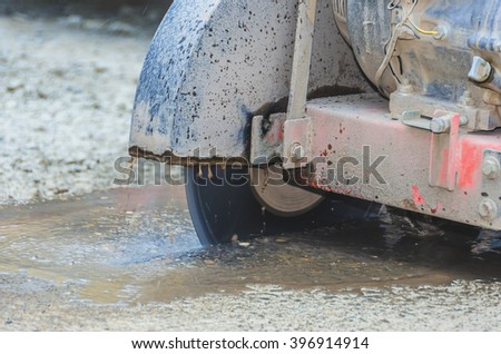 Cutting concrete machine in action at reconstruction area.Closeup shoot. - stock photo