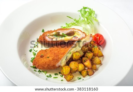 Cutting cordon bleu with cheese, turkey, crackers crumbs, potatoes. - stock photo