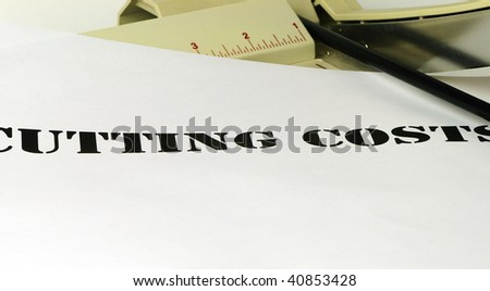 Cutting costs banner under the blade of a paper cutter - stock photo