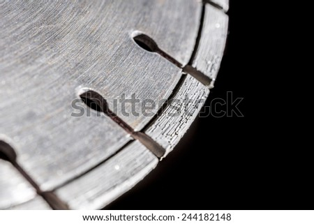 Cutting disk with diamonds, on black background. - stock photo