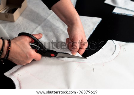 Cutting fabric with a taylors scissors - stock photo