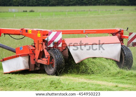 Cutting grass hay with harvesting machine in the field. Detail