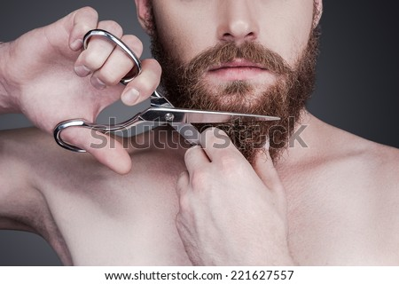 Cutting his perfect beard. Close-up of handsome young shirtless man cutting his beard with scissors while standing against grey background