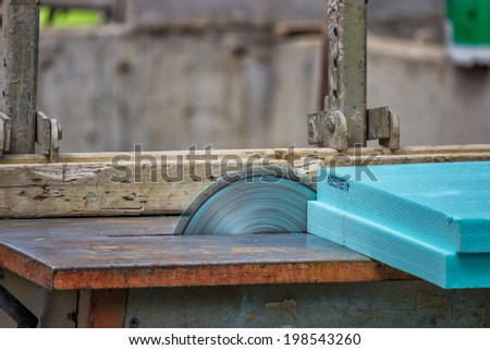 Cutting insulation foam with cutting machine. Selective focus and motion blur. - stock photo