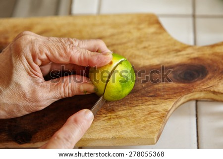 Cutting lime on the wooden cutting board - stock photo