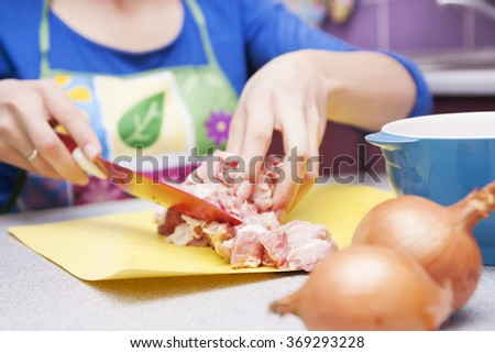 cutting meat and onions in the kitchen at home