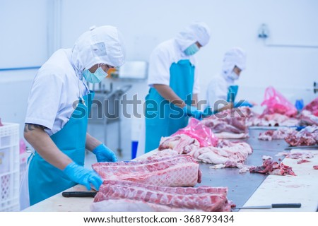 cutting meat slaughterhouse workers in the refrigerator - stock photo