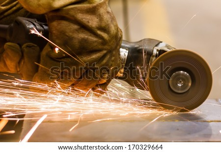 Cutting metal by electric wheel grinding  - stock photo