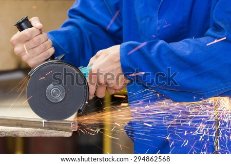 Cutting metal tube by grinder process - stock photo