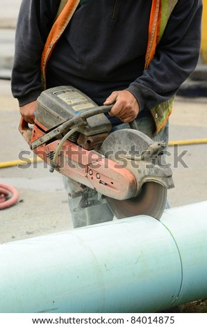 Cutting new plastic pipe to repair a 12 inch water main failure on Harvard Ave in Roseburg OR