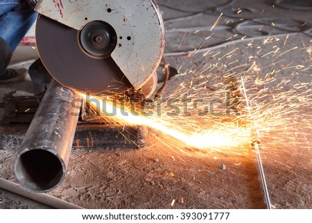 Cutting of a steel with splashes of sparks at construction site.