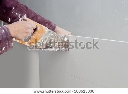 cutting plasterboard plaster hand with grunge dirty saw - stock photo