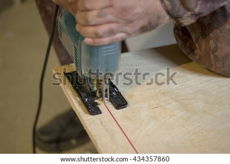 Cutting plywood with a jigsaw on the red line