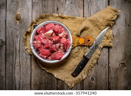 Cutting raw meat a large knife. On a wooden table. Top view - stock photo
