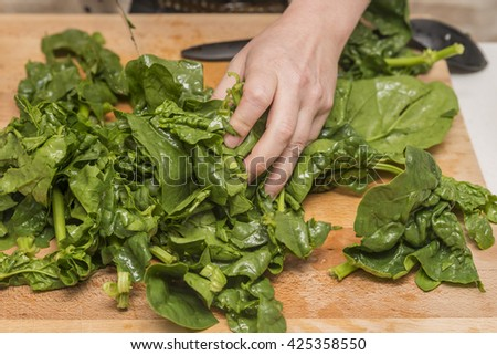 Cutting spinach on a wooden cutting board with a kitchen knife
