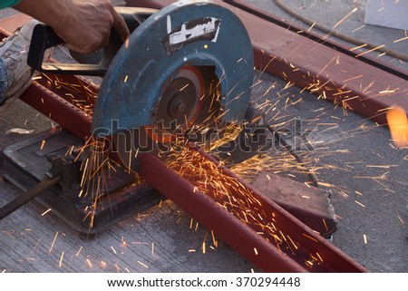 Cutting Steel channel (steel C chanel) with grinder. Sparks while grinding iron - stock photo