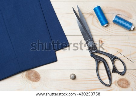 Cutting textile or fine cloth with a tailor scissors on wooden table. Sewing tools - stock photo