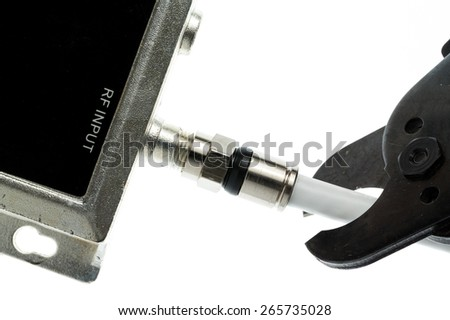 Cutting the cable connection to coax connector illustrating people cancelling cable TV service - stock photo