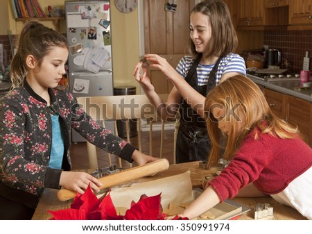 Cutting the Dough. Three sisters are working cooperatively, almost on top of each other, in a small space to cut out the gingerbread shapes ready for baking.