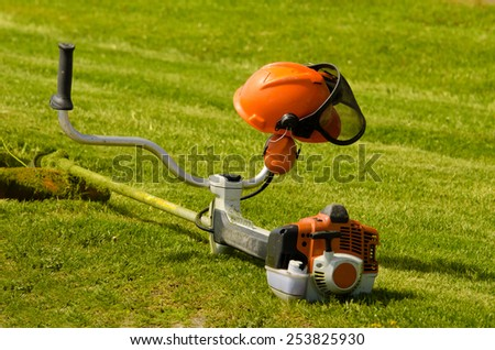 Cutting the grass and helmet - stock photo