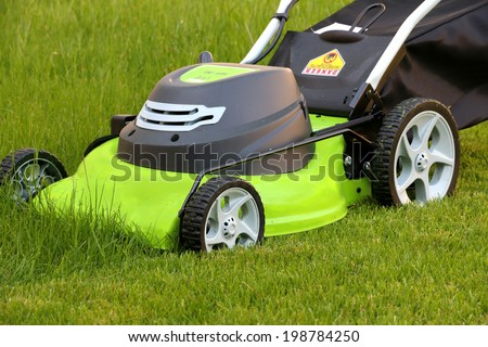 cutting the grass with electric lawn mower landscaping - stock photo