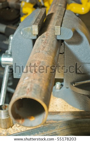 cutting the pipe in a vise - stock photo