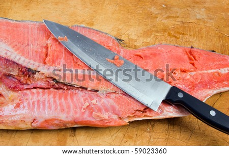 Cutting the salmon with a knife. fish