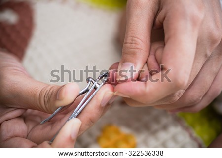 cutting the toenails on both sides of a newborn babies - stock photo