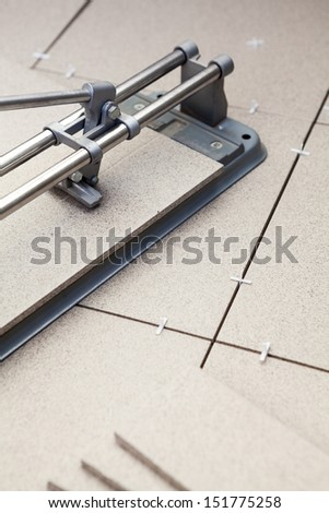 Cutting tiles with tile-cutter on floor when laying floor - stock photo