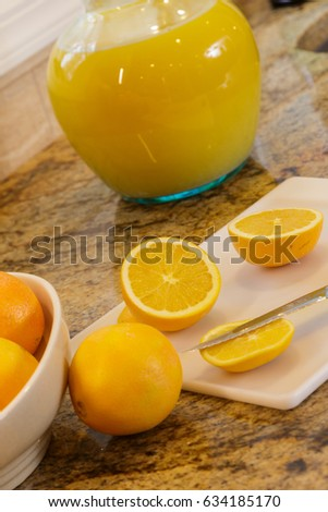 Cutting up oranges for orange juice.
