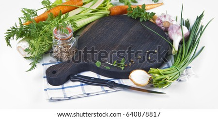Cutting wooden board with vegetables on white