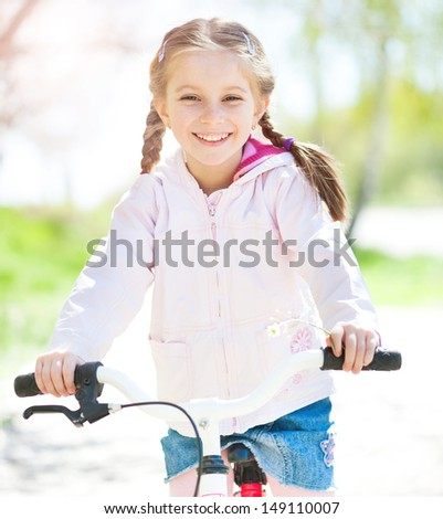 cuye little girl on her pink bike on the road. close-up