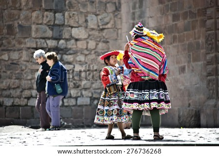 CUZCO, PERU, AUGUST 1 - Quechua Indians break from posing with tourists, drinking sodas - August 1, 2011 in Cuzco, Peru - stock photo