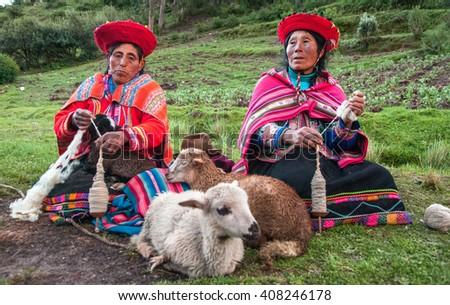 CUZCO, PERU - CIRCA 2007: Women and Lamb. Peruvian women spinning yarn .The Peruvian women in traditional  clothes weave a yarn, sitting on a grass near sheep - stock photo