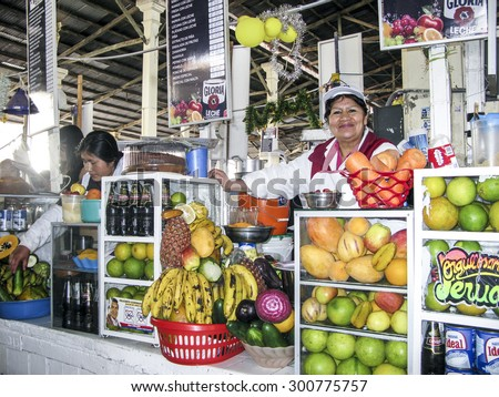 CUZCO, PERU - JAN 18, 2015: friendly local woman sells fresh juices to tourists at the central market in Cuzco, Peru. Beside local fruit she also offers soft drinks.
