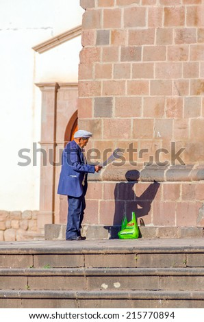 CUZCO, PERU, MAY 1, 2014: Elderly local man reads a poster in front of San Francisco church - stock photo