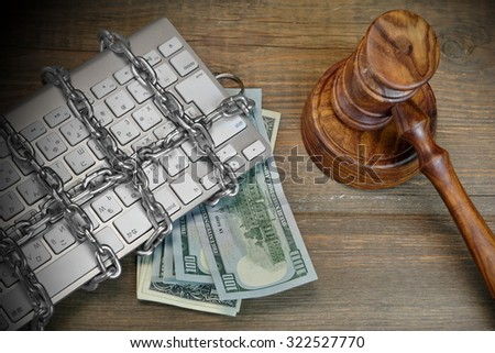 Cyber Crime Concept, Judges Gavel And Keyboard Is Wrapped By Chain On The Rough Brown Wood Table - stock photo