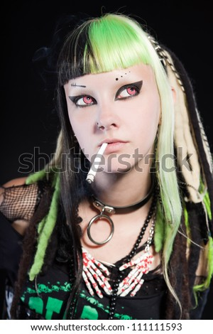 Cyber punk girl with green blond hair and red eyes isolated on black background. Expressive face. Smoking a cigarette. Studio shot.