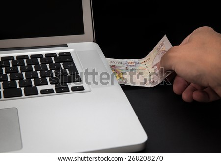 Cyber theft concept shot with laptop and money - stock photo