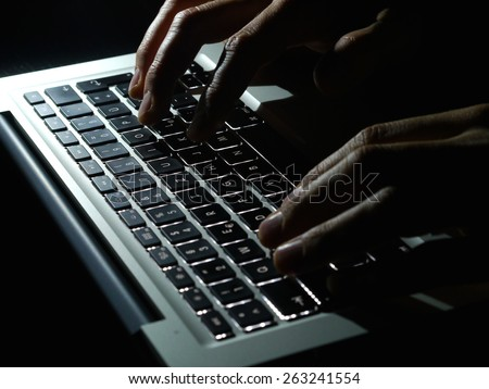 Cybercrime - two Hands on keyboard in the dark - stock photo
