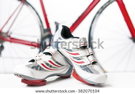 Cycling and sport Concept. Sport Cycling Shoes with Cleats and Covers On Against Red Professional Road Bike. Horizontal Image - stock photo