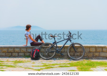 Cycling - Biker girl sitting at seaside, woman fitness, healthy lifestyle