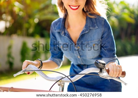 Cycling concept. Close up of smiling young woman riding the bicycle. - stock photo