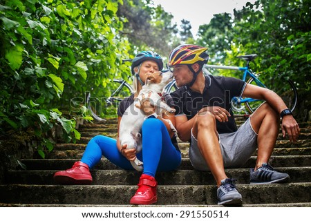 Cycling family with their dog. - stock photo