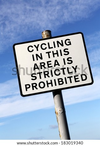Cycling in this area is strictly prohibited sign' against a partly cloudy sky. - stock photo