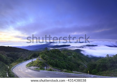 Cycling mountain road. Misty mountain bike road in high mountains. High mountain bike road is being covered with fog. Cloudy sky with mountain road view in sunrise. - stock photo
